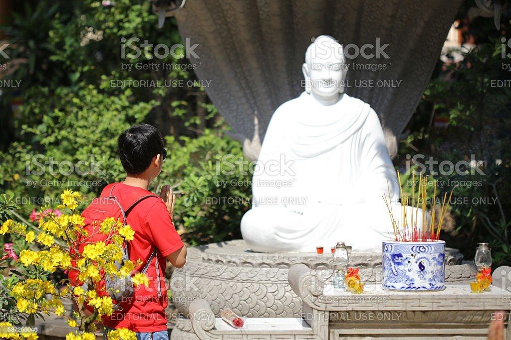The boy is praying Buddha Statue in pagoda stock photo