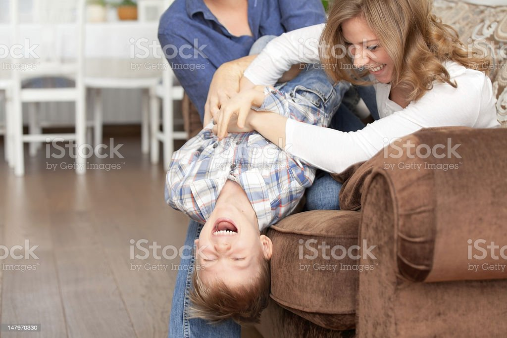 The boy laughs with parents stock photo