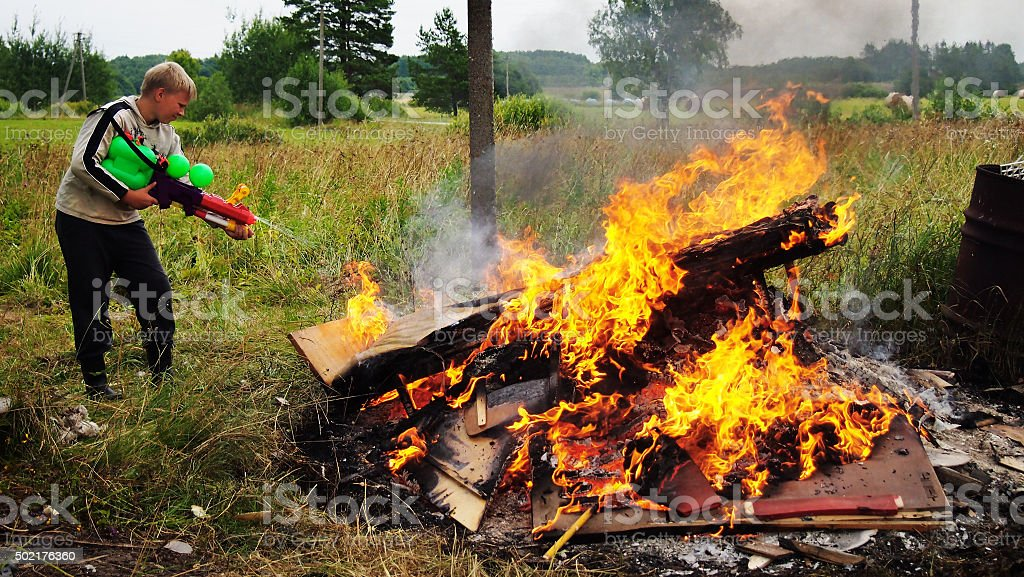 The boy puts out the flames stock photo