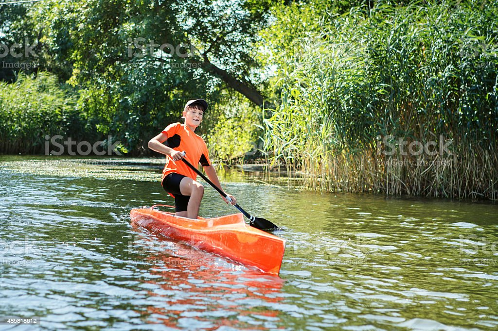 The boy rowing in a canoe on the river. stock photo