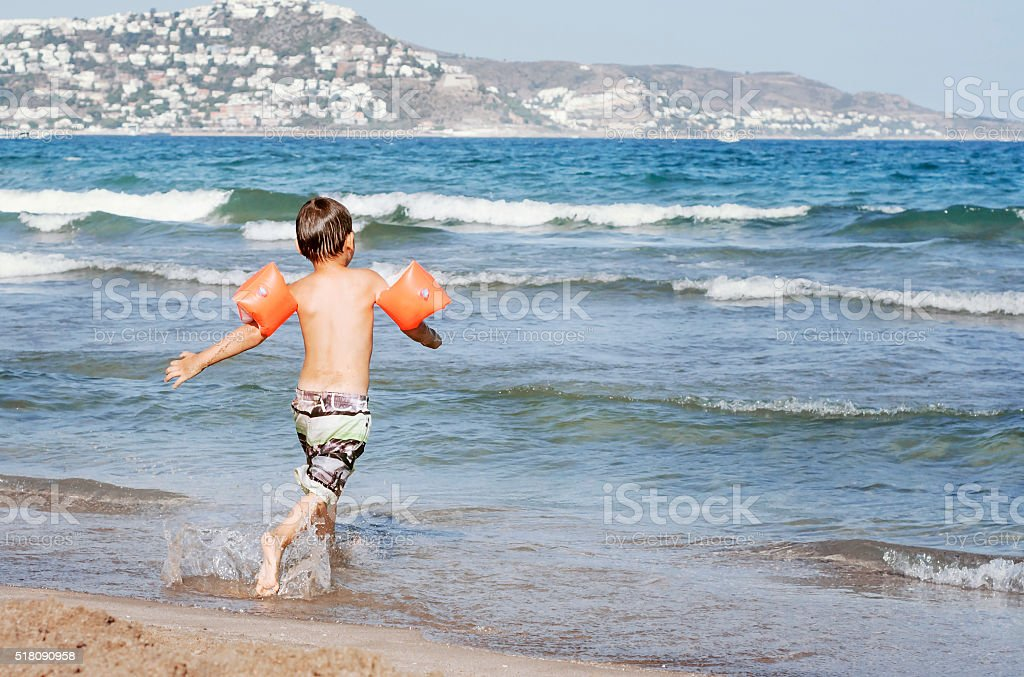 The boy runs to the sea with armbands for swimming. stock photo