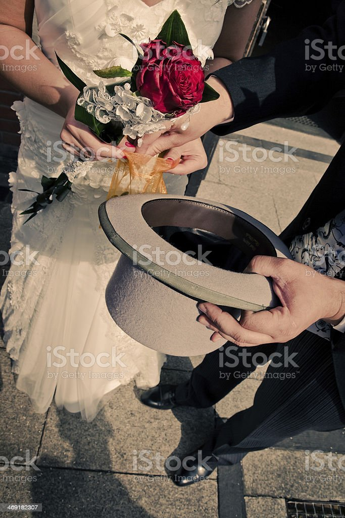 The bride and groom raise coins stock photo