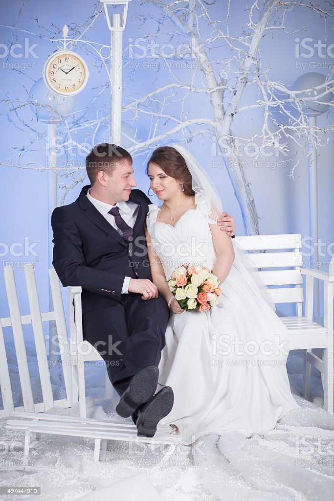 the bride and groom sit on the bench stock photo