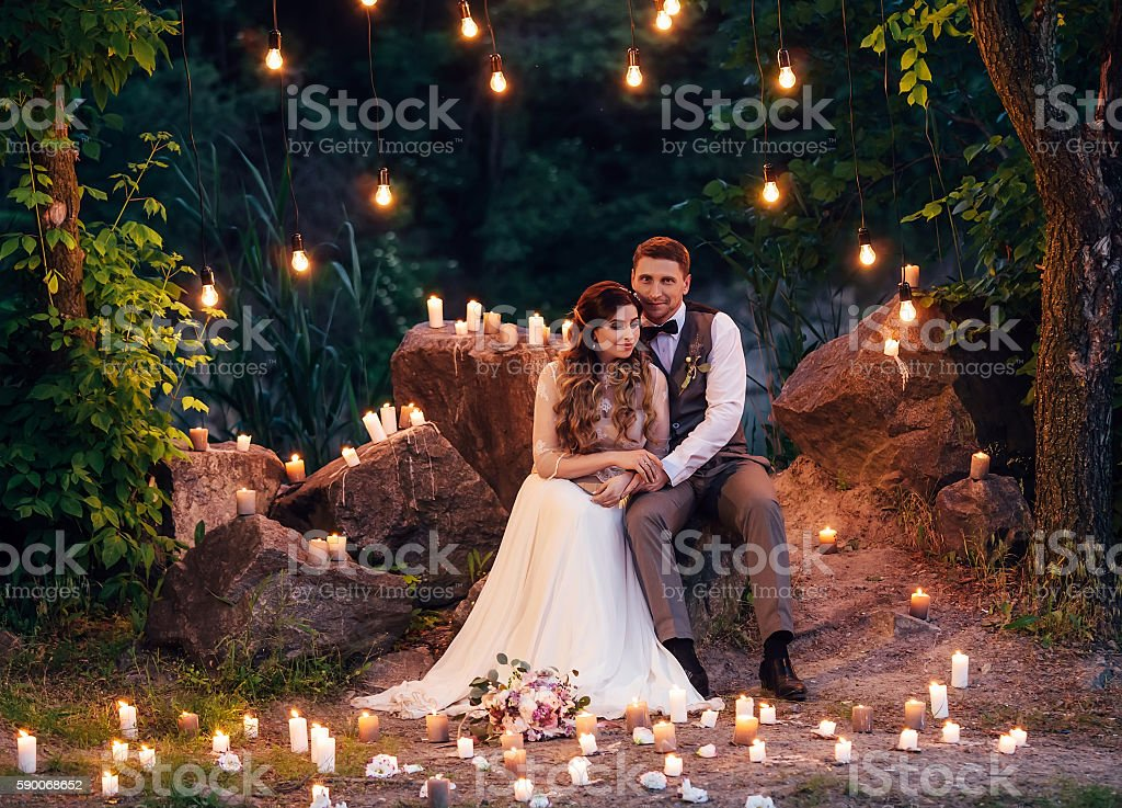 The bride and groom sitting on the rock . stock photo