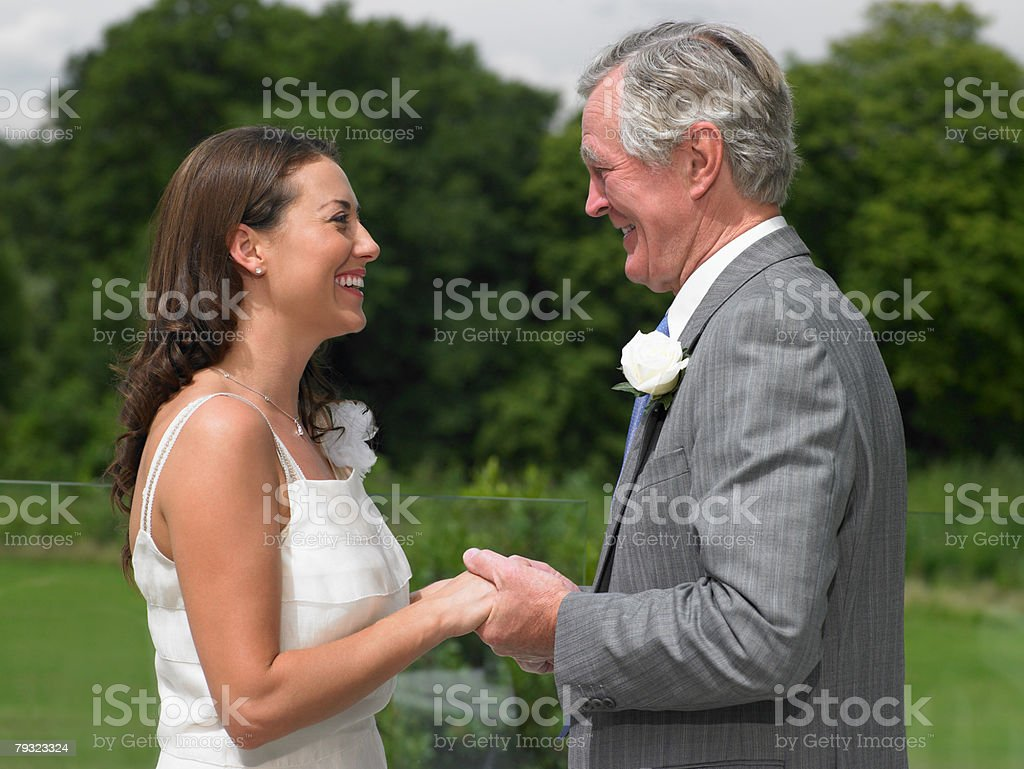 The bride and her father holding hands stock photo
