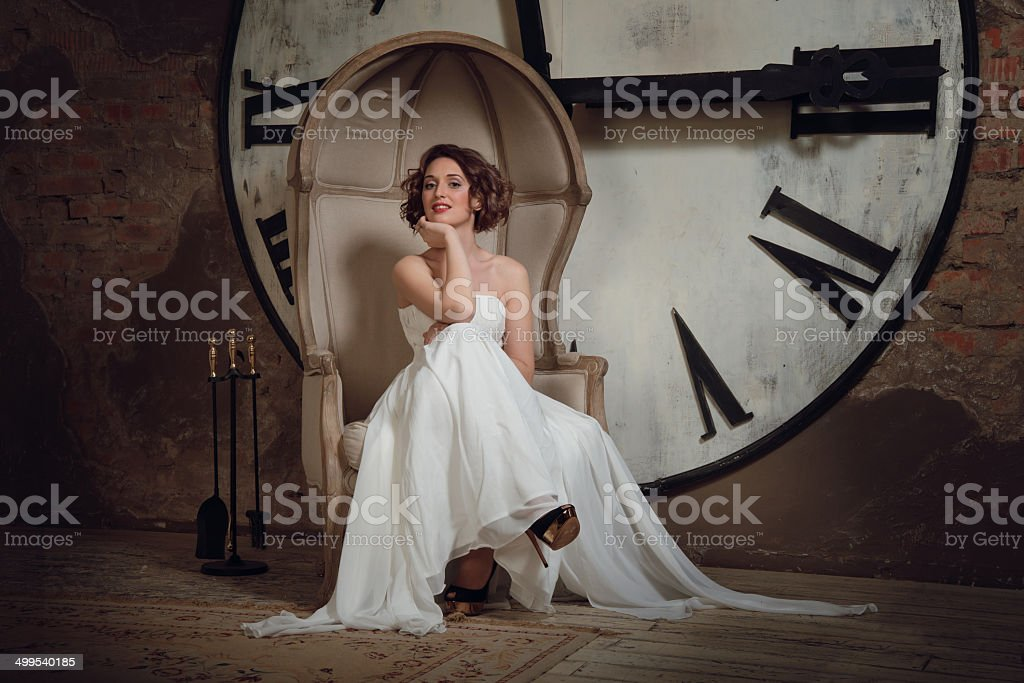 The bride in a chair on background of clocks royalty-free stock photo
