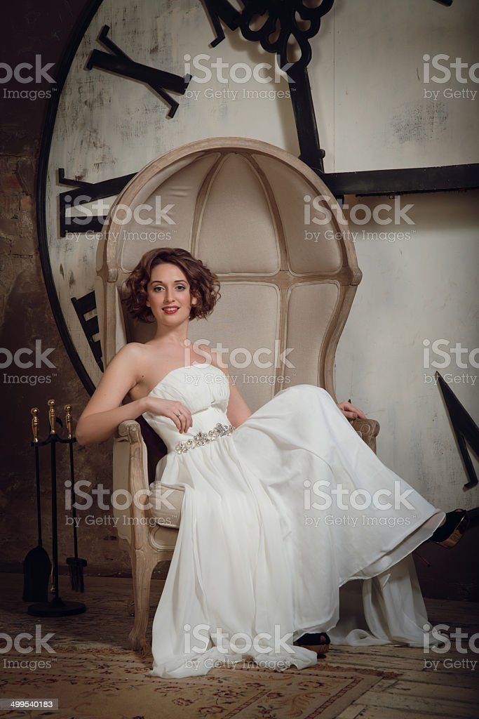The bride in a chair with fireplace tool set. royalty-free stock photo