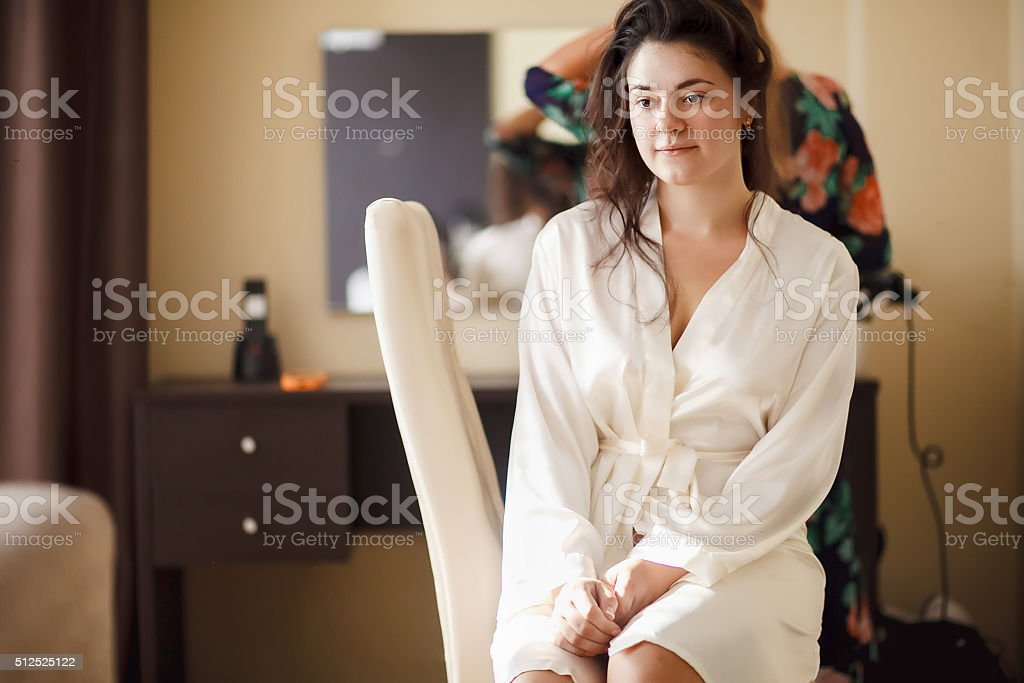 The bride in white bathrobe with her hair done at stock photo