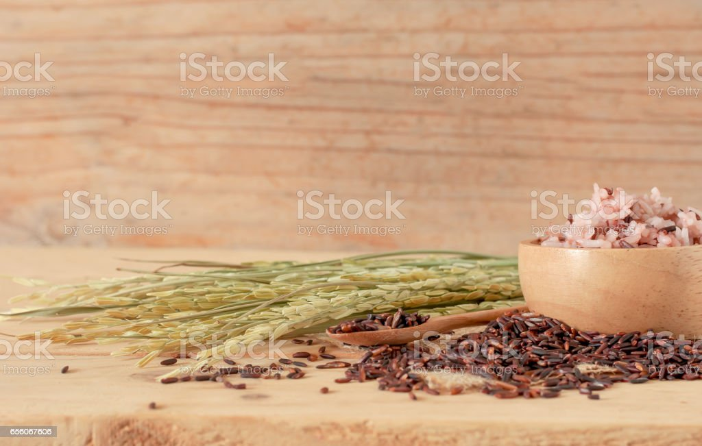 the brown rice in bowl with ear of pappy rice on wooden table stock photo