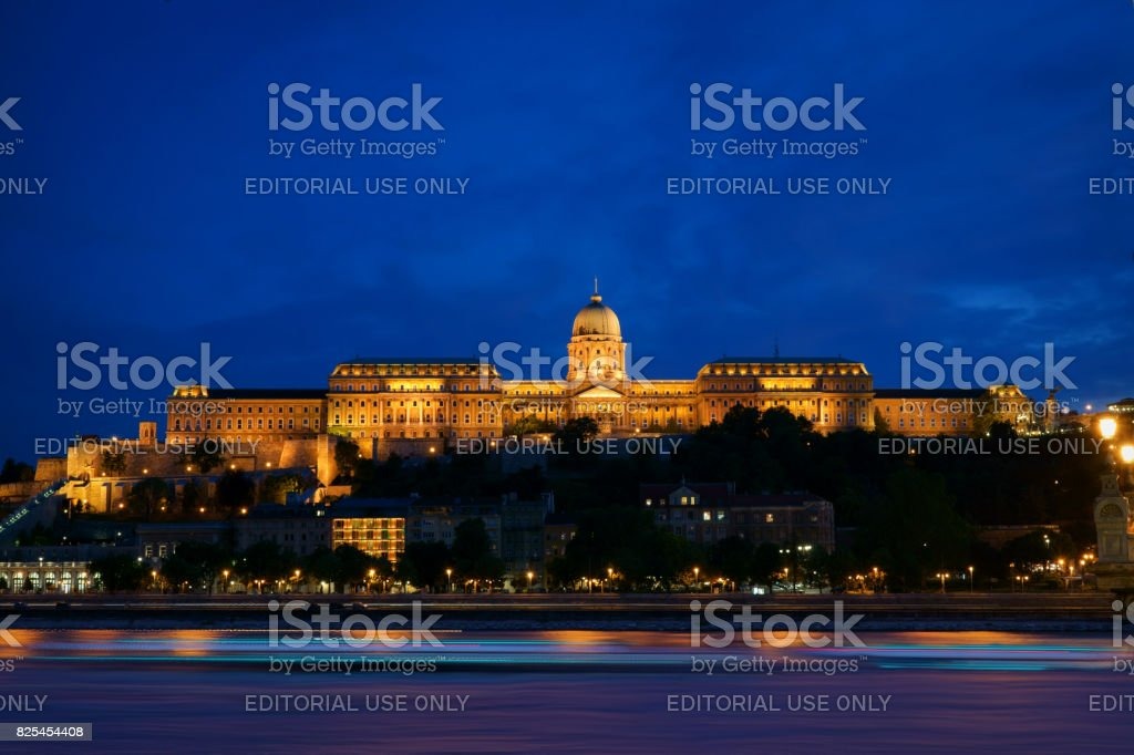 The Buda Castle on Danube river bank during the blue hour with magnificent light shining in Budapest city stock photo