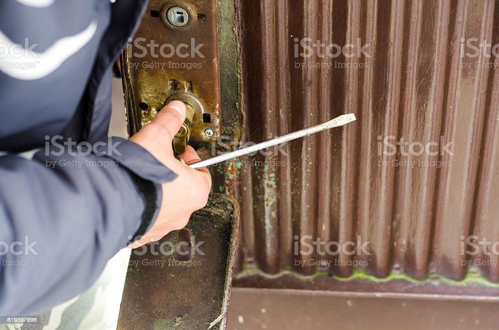 The burglar destroyed the lock on the old metal door. stock photo