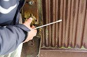 The burglar destroyed the lock on the old metal door.