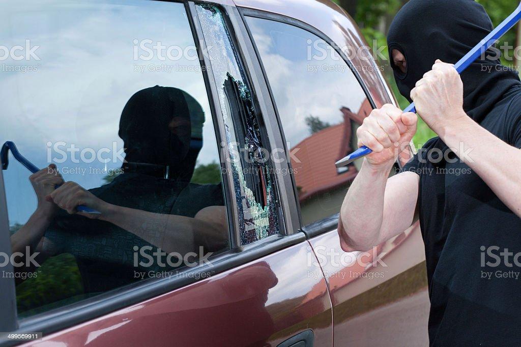 The burglar smash the glass of the car stock photo