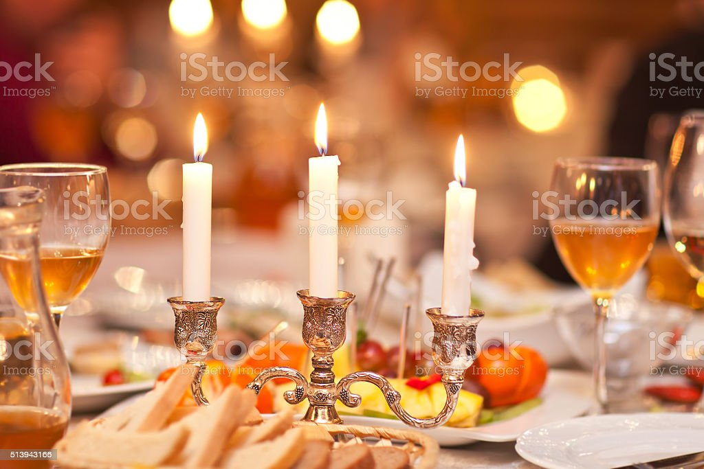 The burning candles in a candlestick on a festive table stock photo