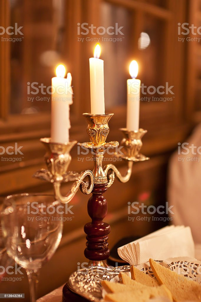 The burning candles in a candlestick on a  table stock photo