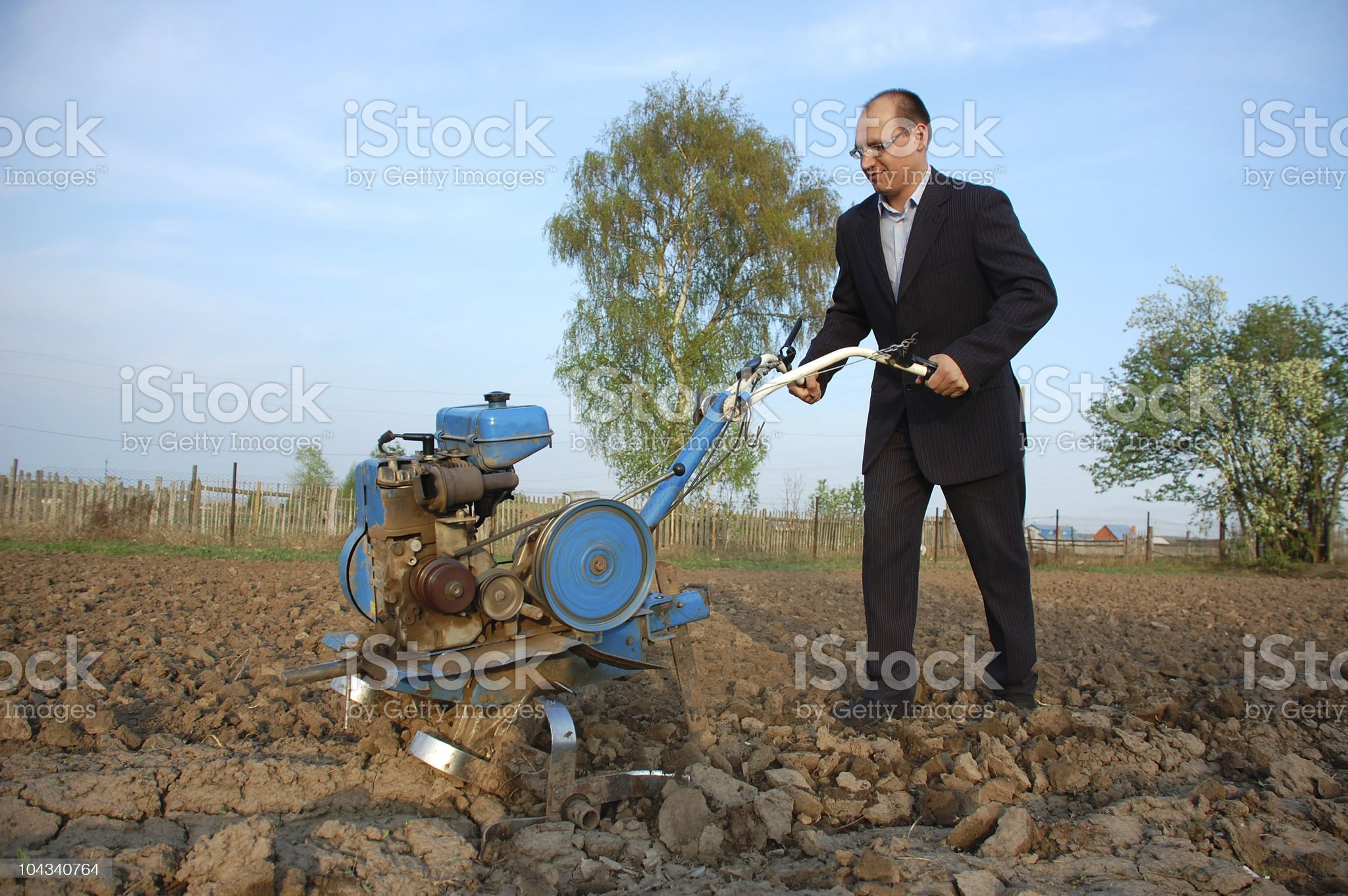 The businessman behind a tractor. royalty-free stock photo