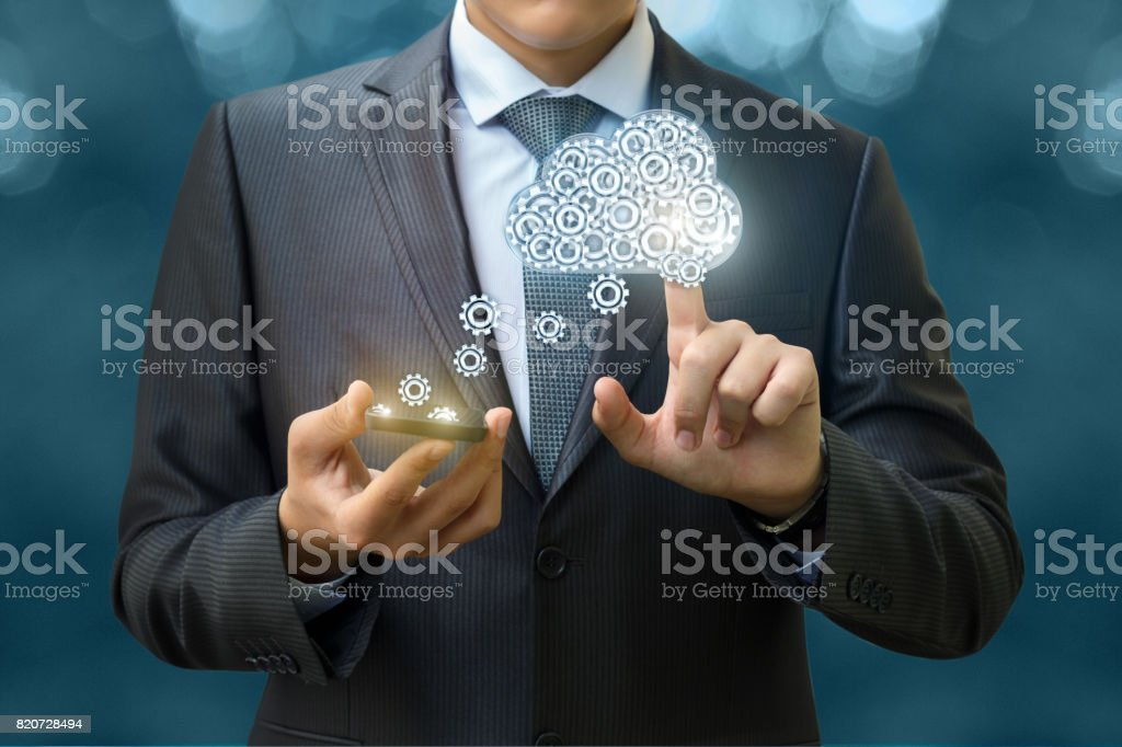 The businessman downloads data from the cloud . stock photo
