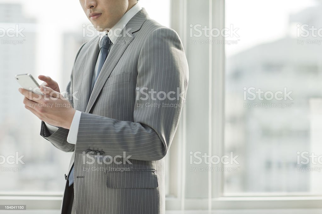 The businessman who operates a smartphone royalty-free stock photo