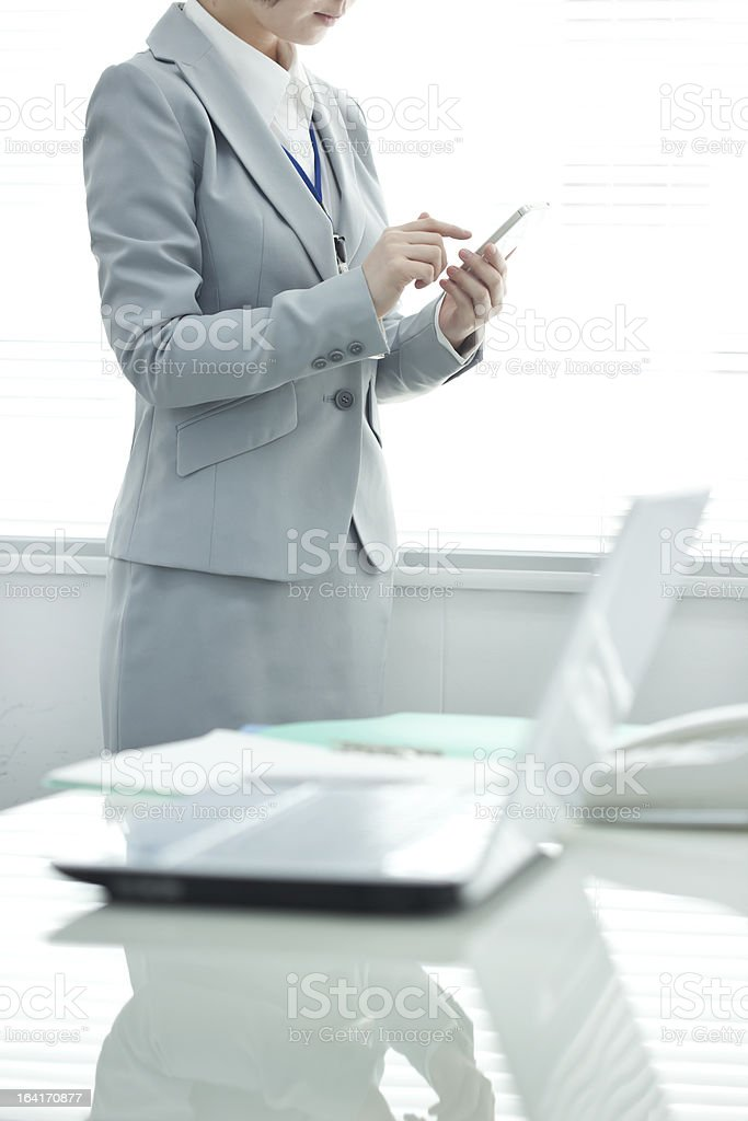 The businesswoman who operates a smartphone royalty-free stock photo
