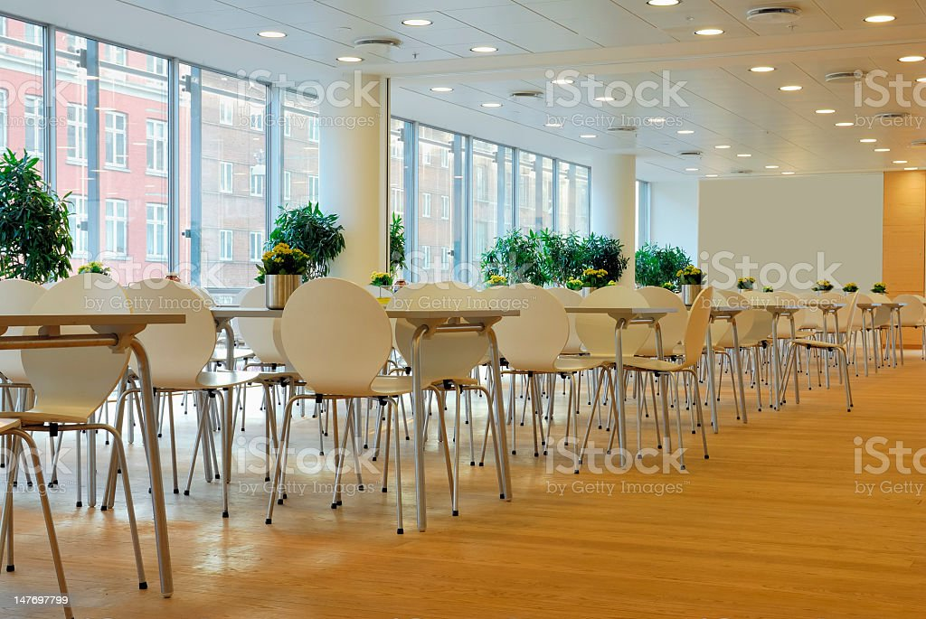 The cafeteria interior had light brown tables and chairs stock photo