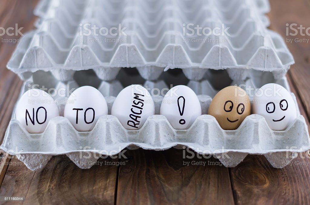 The cardboard egg tray with chicken eggs. Social concept. Antiracism. stock photo