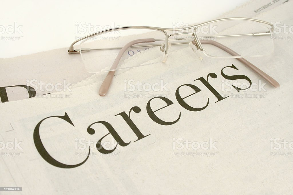The careers section of the newspaper with a pair of glasses stock photo