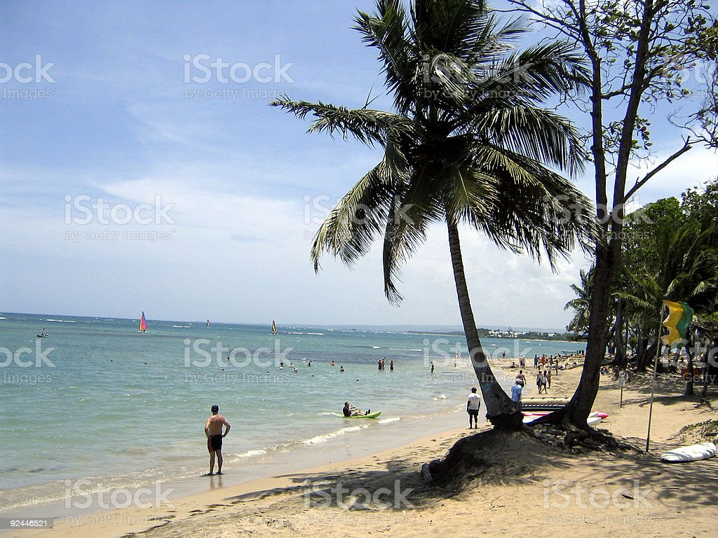 The Caribbean beach with people by the shore  stock photo