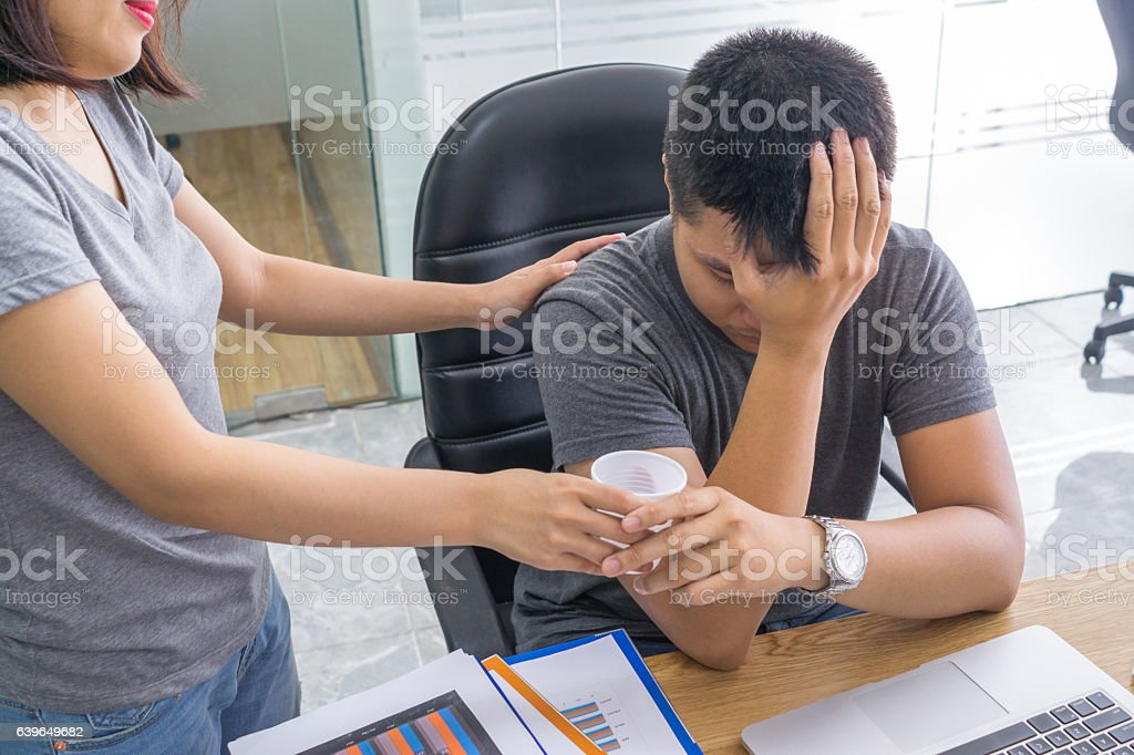The caring woman brings water to his sickly workmate stock photo