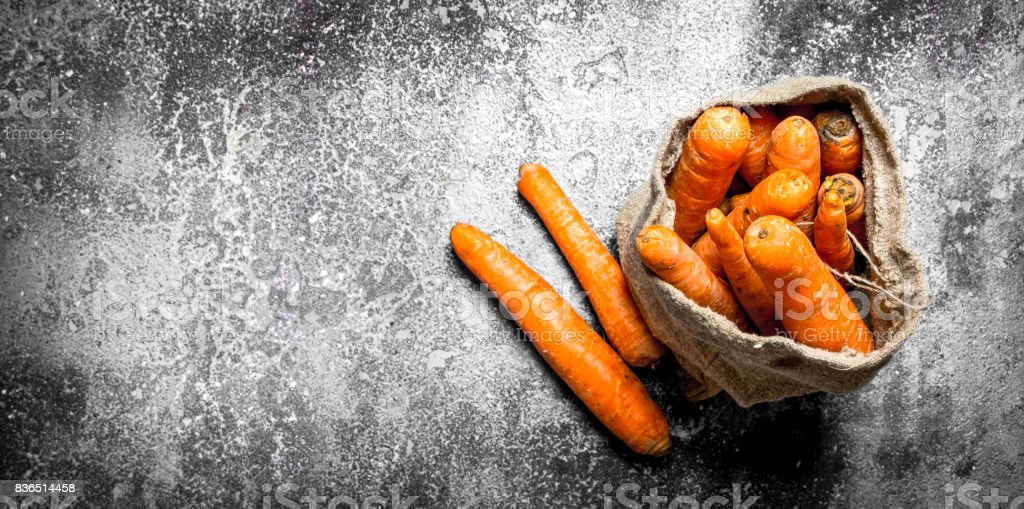The carrots in the old bag. On rustic background. stock photo
