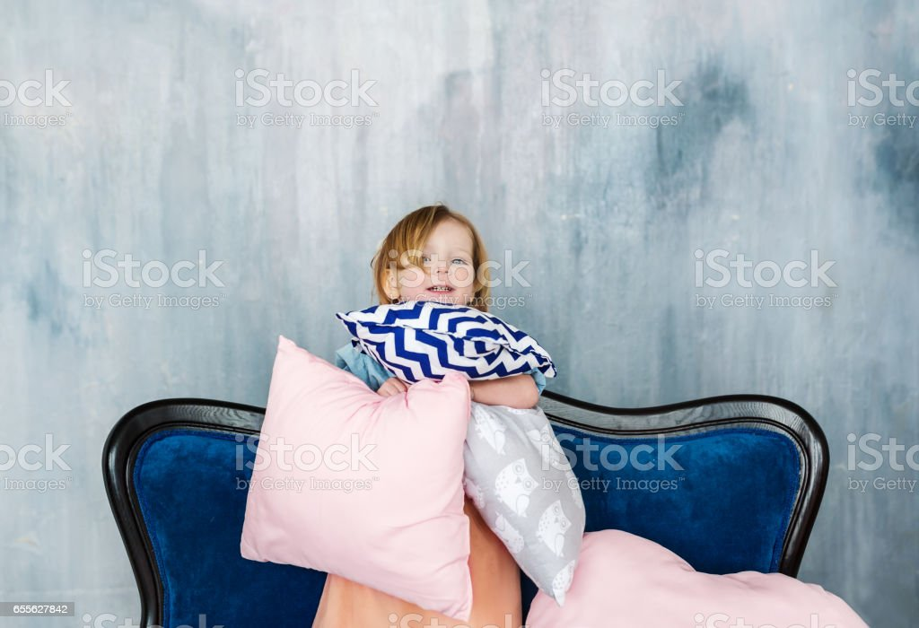 The charming child stand on sofa with pillows in hands. stock photo