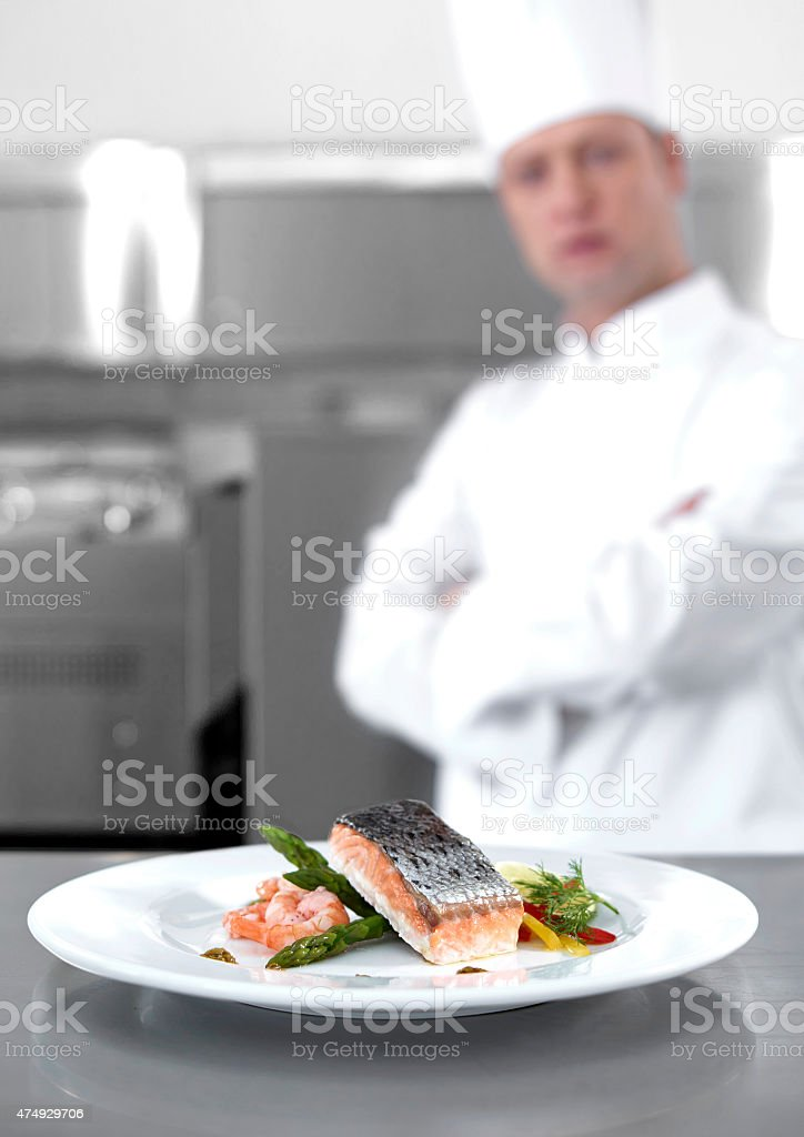 The chef looking at salmon dish stock photo