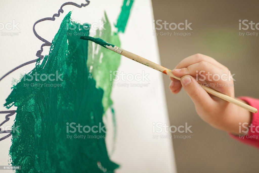 the child draws paints on paper. children's drawing. a stock photo