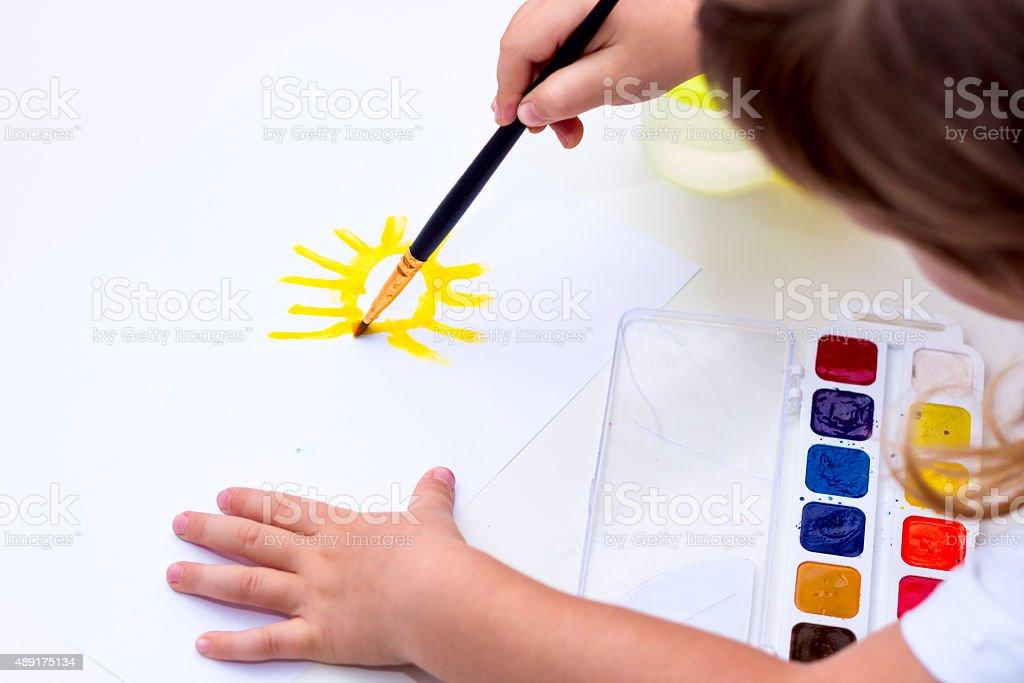 The child draws the sun. stock photo