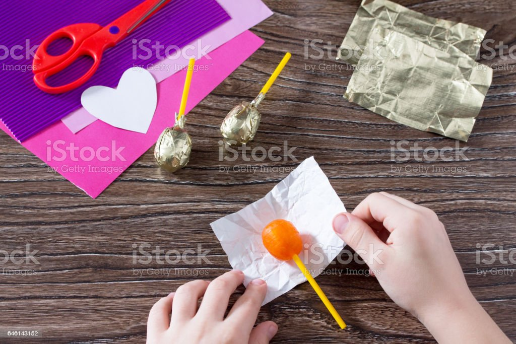 The child glues the to the paper card details. The child makes a postcard butterfly hearts and Lollipop. Children's art project, a craft for children. Crafts for kids. stock photo