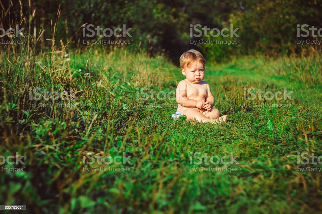 The child is sitting on the grass stock photo
