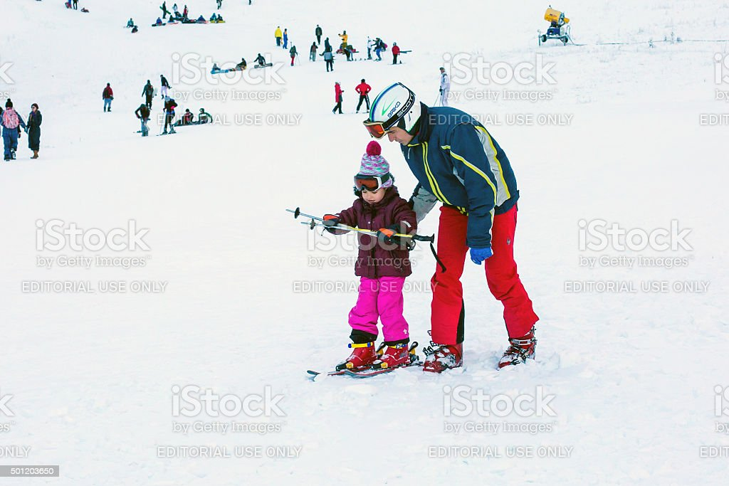 The child learning to ski and man on the slope stock photo