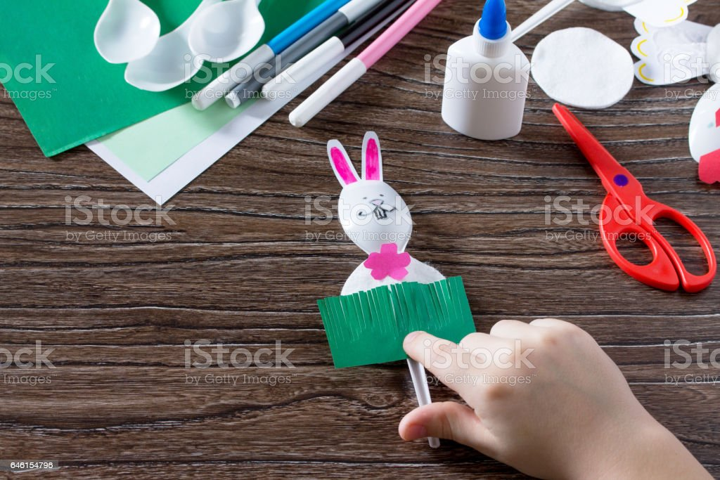 The child sticks gift items. Children's Easter gift toy Rooster and the Easter Bunny. Made by hand. Children's Art Project, needlework, crafts for children. stock photo