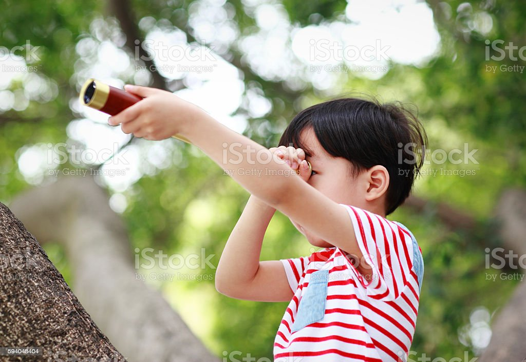 The child uses a telescope on a tree stock photo