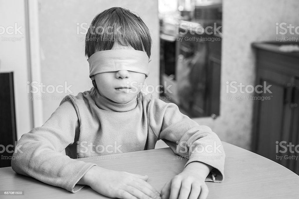 The child was blindfolded at home. stock photo