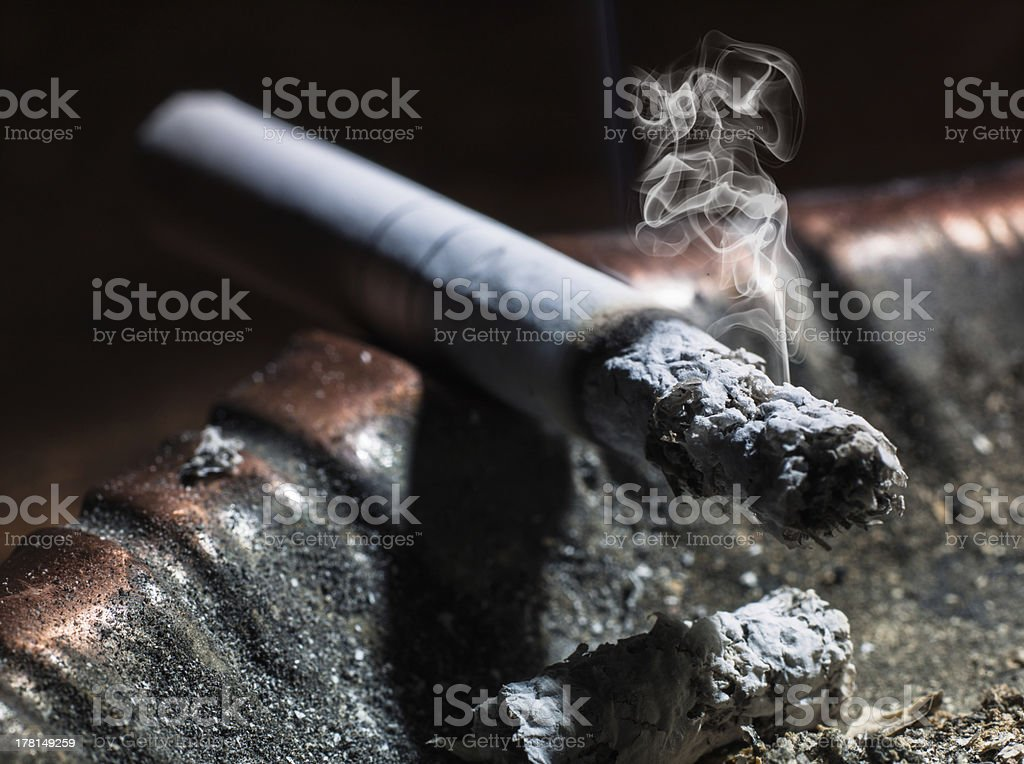 the cigarette emitting smoke burning in an ashtray royalty-free stock photo
