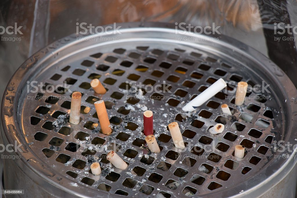 The cigarette stubs in the ashtray. stock photo