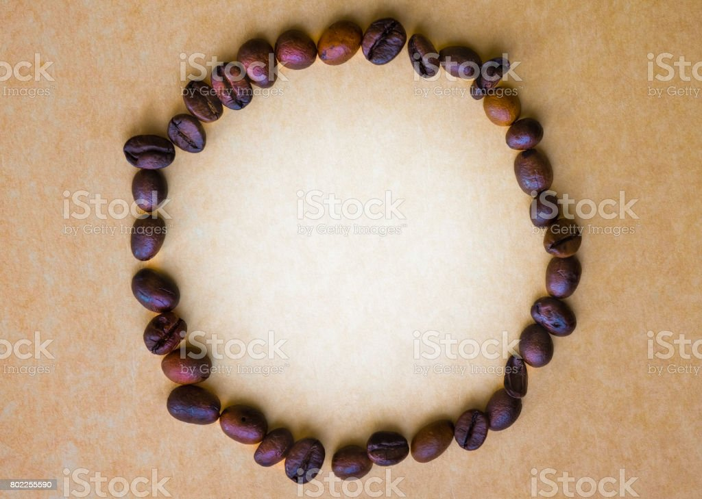 The circle frame of coffee beans on vintage background, add some text in center. stock photo