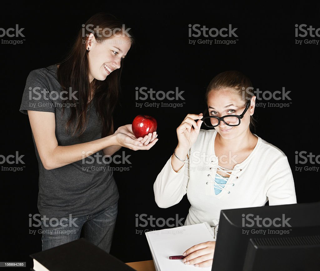 The classic bribe: student offers teacher an apple royalty-free stock photo