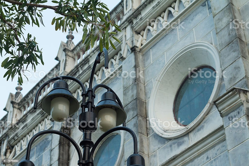 The classical road lamp with gothic church stock photo