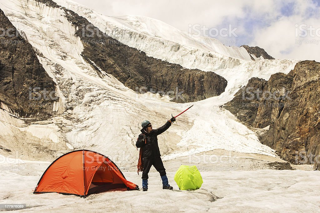 The climber costs on glacier near tent stock photo