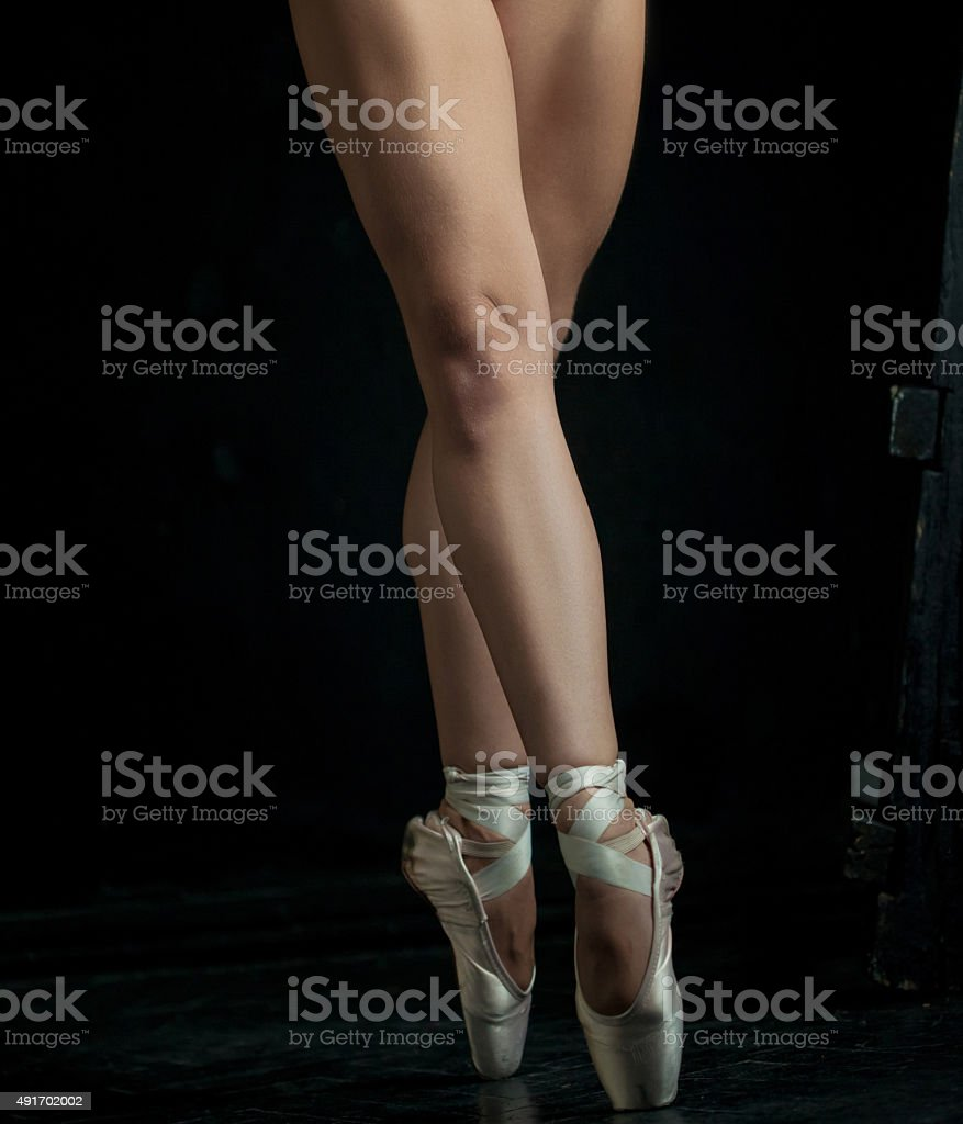 The close-up feet of young ballerina in pointe shoes stock photo