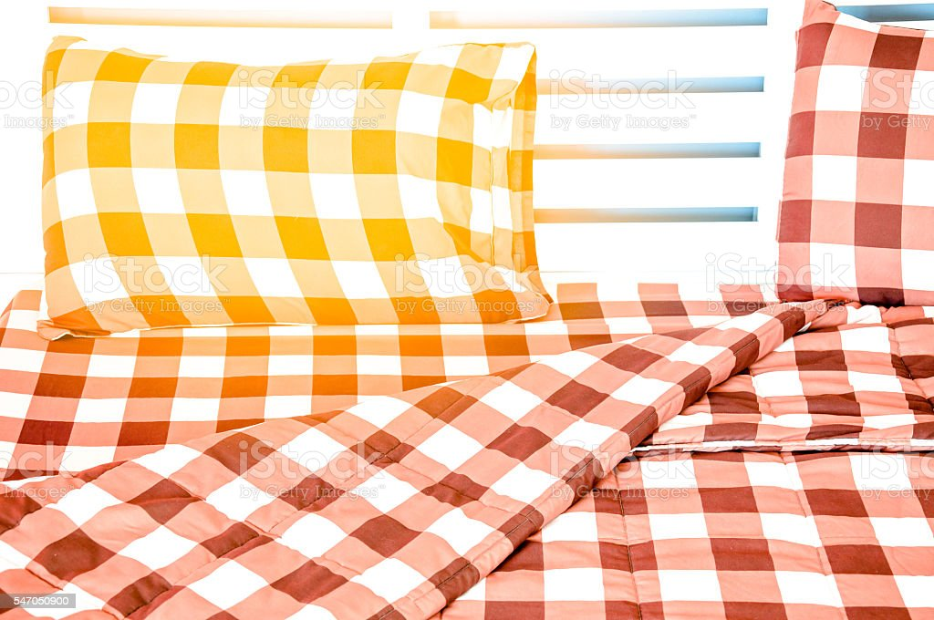 the closeup of bed in small bedroom with warm light stock photo