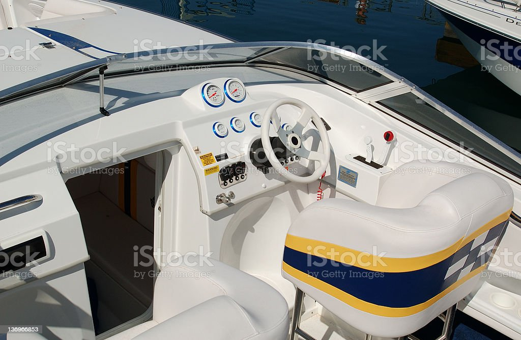 The cockpit of a white, blue, and yellow boat royalty-free stock photo