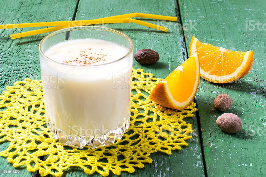 The cold milkshake with orange juice, ice cream and nutmeg stock photo