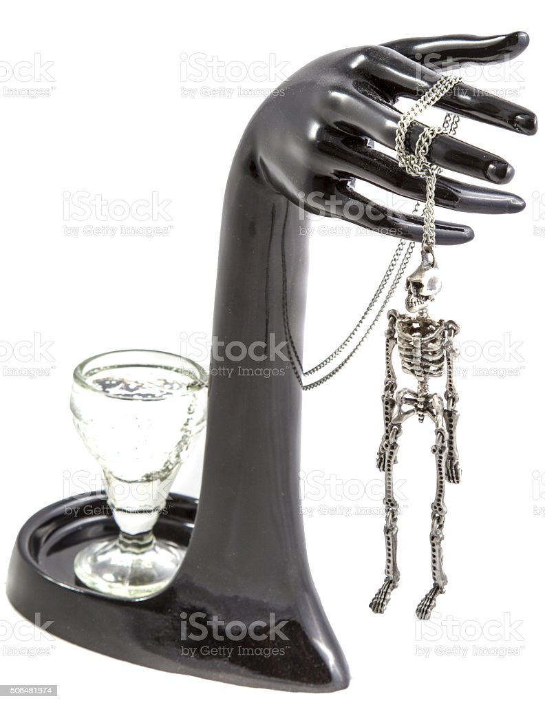 The composition of a glass, hand and hung the skeleton stock photo